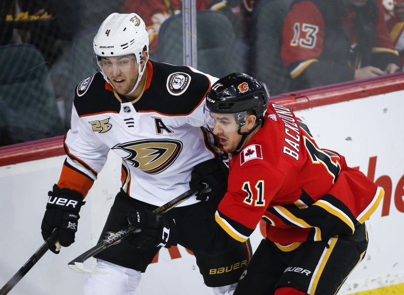 Anaheim Ducks' Cam Fowler, left, and Calgary Flames' Mikael Backlund, of Sweden, chase the puck during the first period of an NHL hockey game Friday, Feb. (Jeff McIntosh/The Canadian Press via AP)