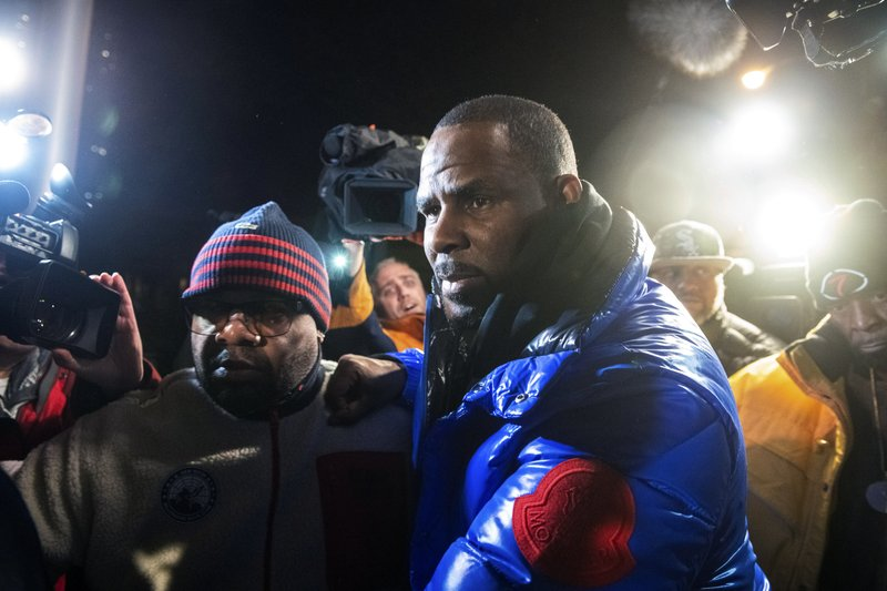 R. Kelly surrenders to authorities at Chicago First District police station, Friday, Feb. 22, 2019.  R&B star R. (Tyler LaRiviere/Chicago Sun-Times via AP)