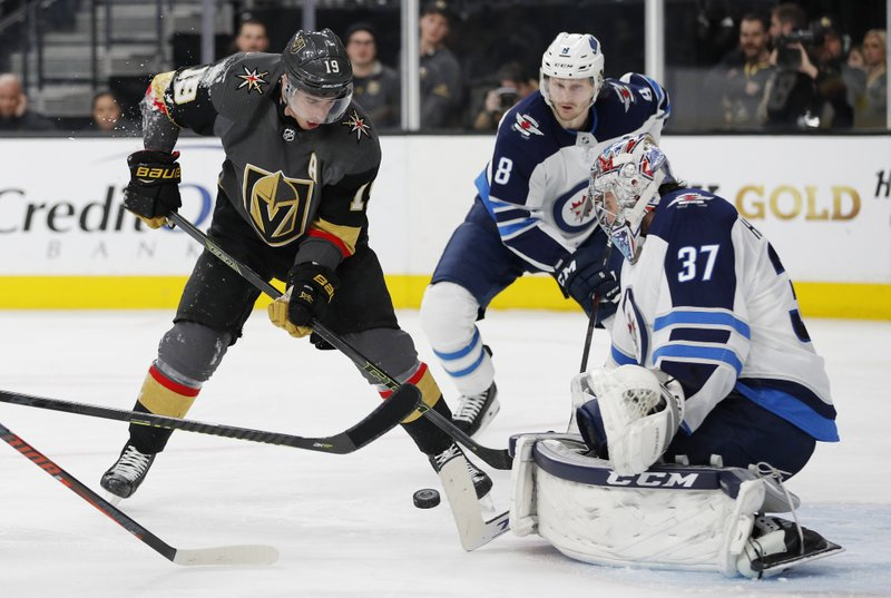 Winnipeg Jets goaltender Connor Hellebuyck (37) blocks a shot by Vegas Golden Knights right wing Reilly Smith (19) during the second period of an NHL hockey game Friday, Feb. (AP Photo/John Locher)