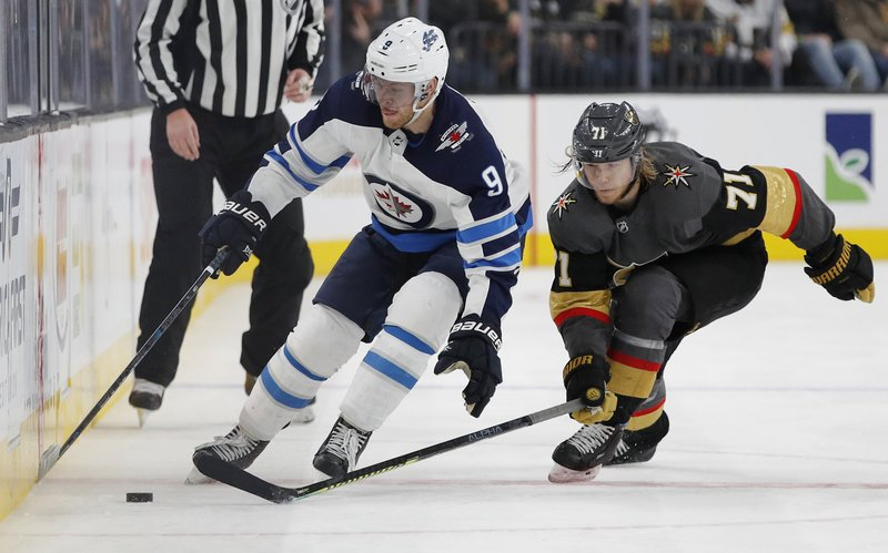 Winnipeg Jets center Andrew Copp (9) and Vegas Golden Knights center William Karlsson (71) vie for the puck during the third period of an NHL hockey game Friday, Feb. (AP Photo/John Locher)