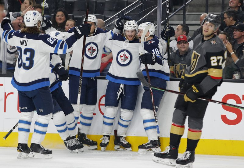 Winnipeg Jets left wing Kyle Connor, second from right at rear, celebrates with teammates after scoring against the Vegas Golden Knights during the first period of an NHL hockey game Friday, Feb. (AP Photo/John Locher)