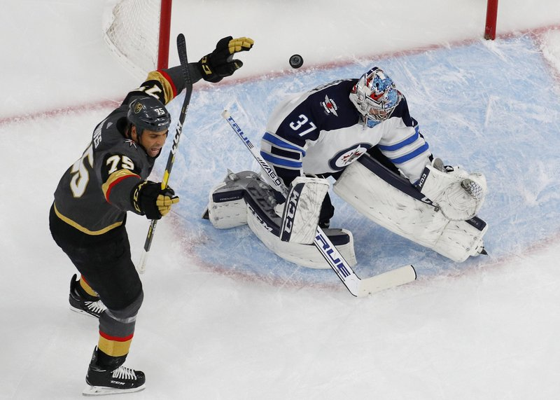 Vegas Golden Knights right wing Ryan Reaves (75) celebrates after center Pierre-Edouard Bellemare scored against Winnipeg Jets goaltender Connor Hellebuyck (37) during the first period of an NHL hockey game Friday, Feb. (AP Photo/John Locher)