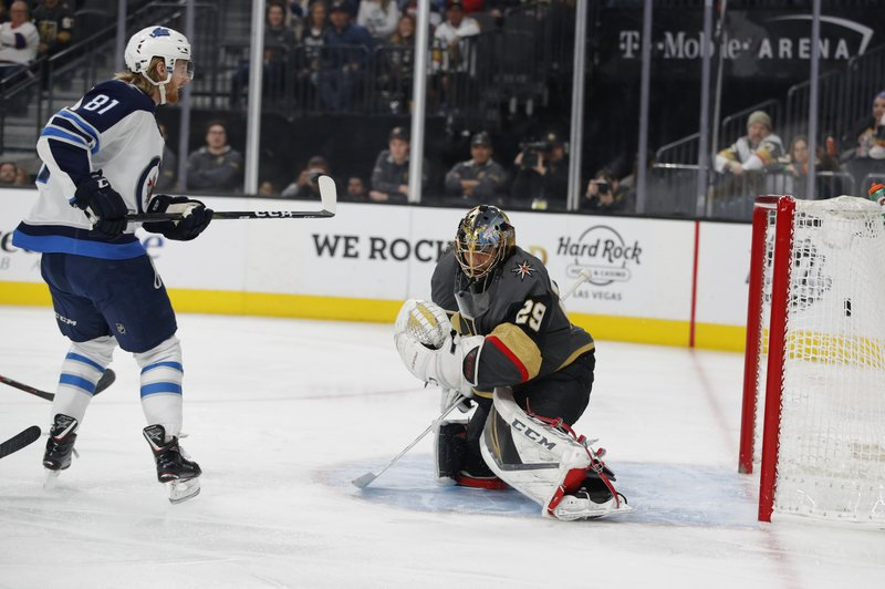 Winnipeg Jets left wing Kyle Connor (81) scores against Vegas Golden Knights goaltender Marc-Andre Fleury (29) during the first period of an NHL hockey game Friday, Feb. (AP Photo/John Locher)