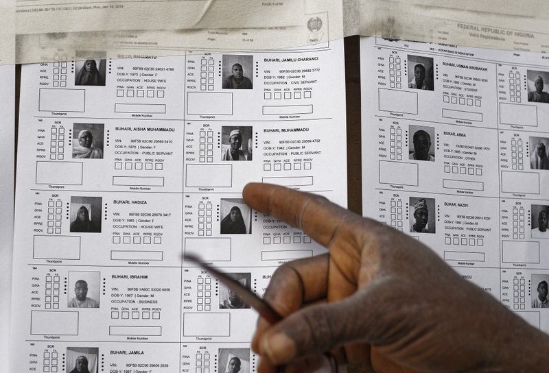 A voter points to the record for President Muhammadu Buhari on a voter registration list, before polls open in his hometown of Daura, in northern Nigeria Saturday, Feb. (AP Photo/Ben Curtis)
