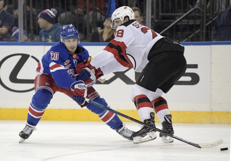 New York Rangers left wing Chris Kreider (20) reaches for the puck as he is checked by New Jersey Devils defenseman Damon Severson (28) during the second period of an NHL hockey game Saturday, Feb. (AP Photo/ Bill Kostroun)