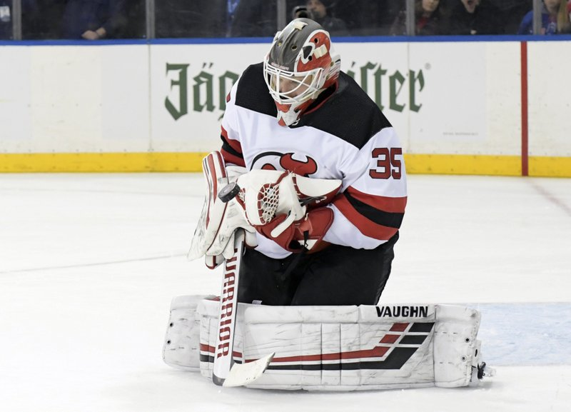 New Jersey Devils goaltender Cory Schneider stops the puck during the second period of an NHL hockey game against the New York Rangers Saturday, Feb. (AP Photo/ Bill Kostroun)