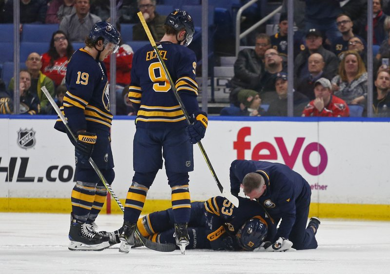 Buffalo Sabres Jake McCabe (19) and Jack Eichel (9) watch as Jeff Skinner (53) is attended to by a trainer during the second period of an NHL hockey game against the Washington Capitals, Saturday, Feb. (AP Photo/Jeffrey T. Barnes)