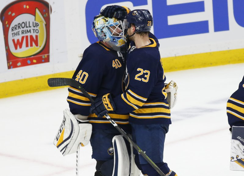 Buffalo Sabres goalie Carter Hutton (40) and forward Sam Reinhart (23) celebrate a 5-2 victory over the Washington Capitals after an NHL hockey game, Saturday, Feb. (AP Photo/Jeffrey T. Barnes)