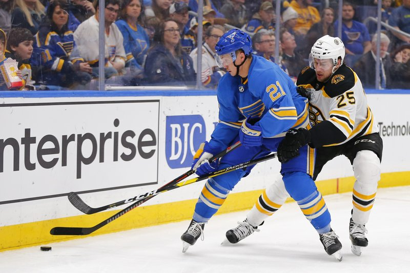 St. Louis Blues' Tyler Bozak, left, fights off Boston Bruins' Brandon Carlo for control of the puck during the second period of an NHL hockey game Saturday, Feb. (AP Photo/Dilip Vishwanat)