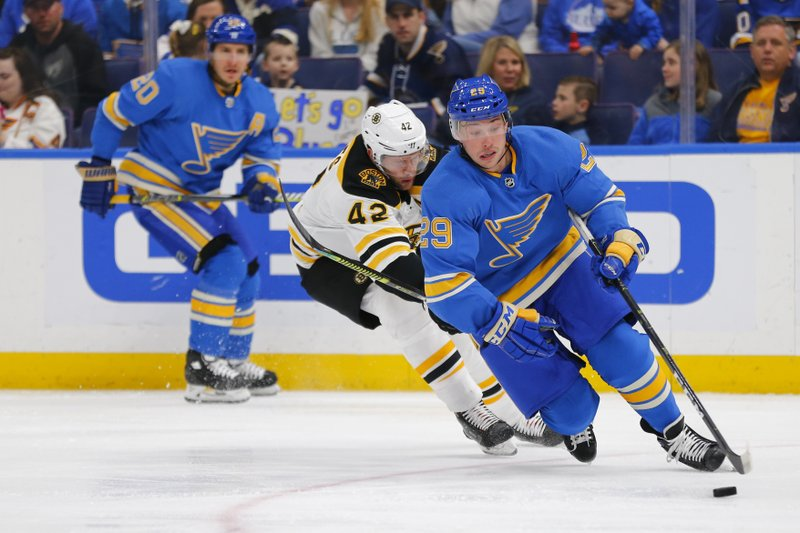 St. Louis Blues' Vince Dunn (29) controls the puck against Boston Bruins' David Backes (42) during the first period of an NHL hockey game Saturday, Feb. (AP Photo/Dilip Vishwanat)