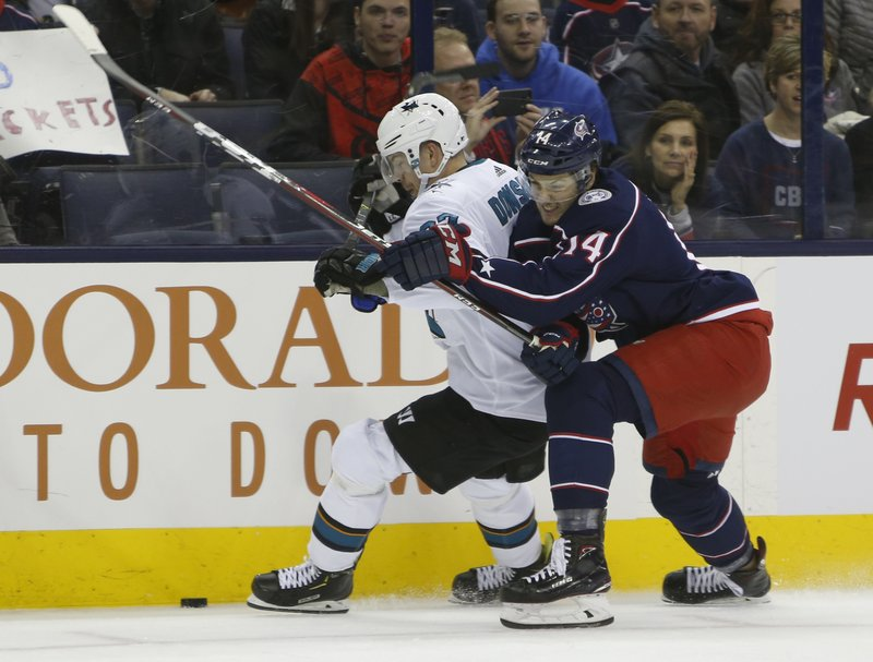 San Jose Sharks' Joonas Donskoi, left, of Finland, and Columbus Blue Jackets' Dean Kukan, of Switzerland, fight for the puck during the first period of an NHL hockey game Saturday, Feb. (AP Photo/Jay LaPrete)