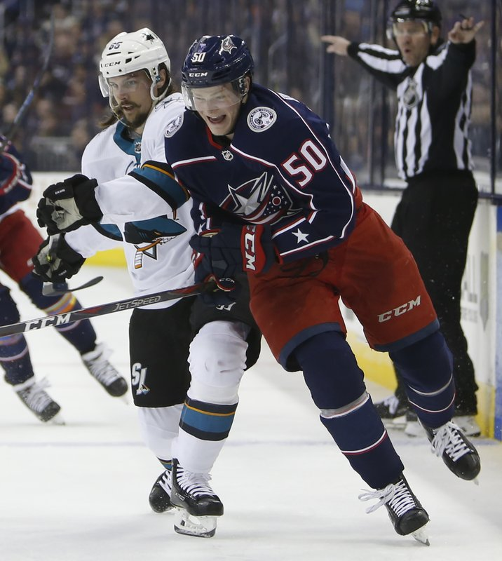 San Jose Sharks' Erik Karlsson, left, of Sweden, and Columbus Blue Jackets' Eric Robinson chase the puck during the second period of an NHL hockey game Saturday, Feb. (AP Photo/Jay LaPrete)