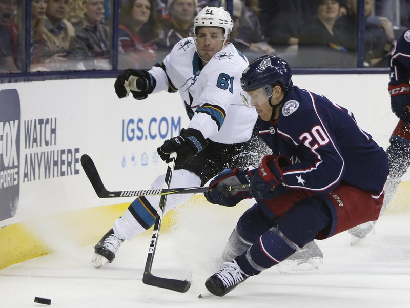 San Jose Sharks' Justin Braun, left, and Columbus Blue Jackets' Riley Nash chase the puck during the second period of an NHL hockey game Saturday, Feb. (AP Photo/Jay LaPrete)