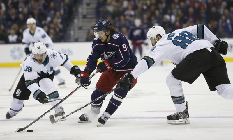 Columbus Blue Jackets' Artemi Panarin, center, of Russia, carries the puck across the blue line between San Jose Sharks' Logan Couture, left, and Brent Burns during the second period of an NHL hockey game Saturday, Feb. (AP Photo/Jay LaPrete)