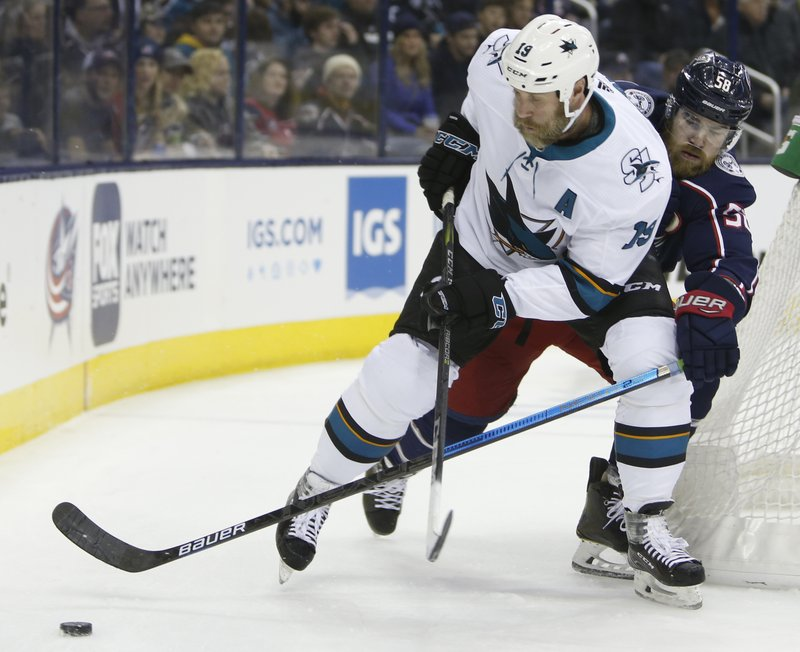 San Jose Sharks' Joe Thornton, left, tries to control the puck as Columbus Blue Jackets' David Savard defends during the first period of an NHL hockey game Saturday, Feb. (AP Photo/Jay LaPrete)