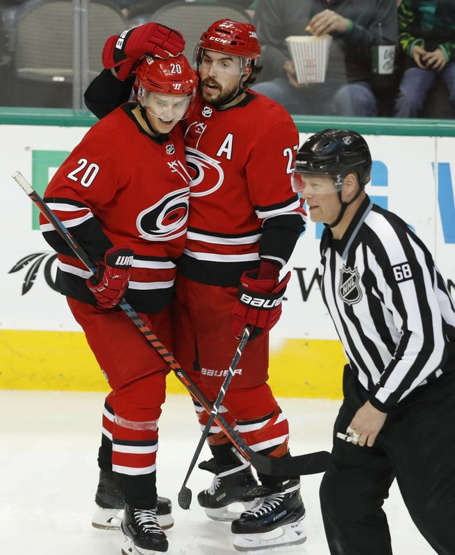 Carolina Hurricanes defenseman Justin Faulk (27) celebrates his goal with Sebastian Aho (20) as linesman Scott Driscoll (68) skates by during the second period of an NHL hockey game against the Dallas Stars in Dallas, Saturday, Feb. (AP Photo/LM Otero)