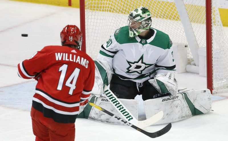 Carolina Hurricanes right wing Justin Williams (14) shoots wide of Dallas Stars goaltender Ben Bishop (30) during the first period of an NHL hockey game in Dallas, Saturday, Feb. (AP Photo/LM Otero)