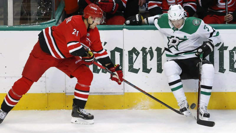 Carolina Hurricanes right wing Nino Niederreiter (21) reaches for the puck against Dallas Stars defenseman John Klingberg (3) during the first period of an NHL hockey game in Dallas, Saturday, Feb. (AP Photo/LM Otero)