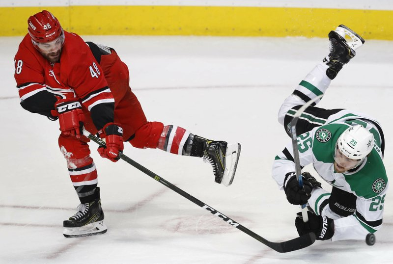 Carolina Hurricanes left wing Jordan Martinook (48) knocks Dallas Stars right wing Brett Ritchie (25) off his feet as they chase the puck during the first period of an NHL hockey game in Dallas, Saturday, Feb. (AP Photo/LM Otero)