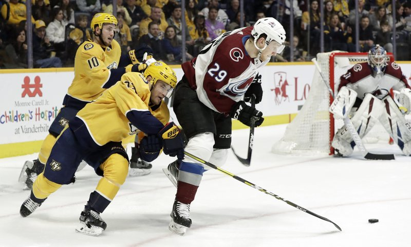 Colorado Avalanche center Nathan MacKinnon (29) blocks Nashville Predators center Rocco Grimaldi (23) from the puck during the second period of an NHL hockey game Saturday, Feb. (AP Photo/Mark Humphrey)