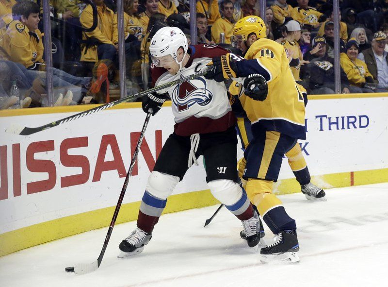 Colorado Avalanche left wing Gabriel Landeskog (92), of Sweden, and Nashville Predators center Calle Jarnkrok (19), of Sweden, compete for the puck during the first period of an NHL hockey game Saturday, Feb. (AP Photo/Mark Humphrey)