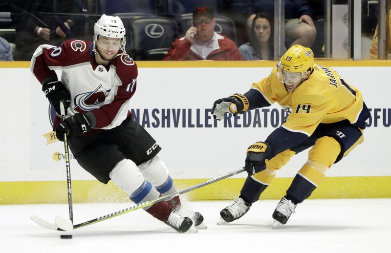 Colorado Avalanche right wing Sven Andrighetto (10), of the Czech Republic, and Nashville Predators center Calle Jarnkrok (19), of Sweden, reach for the puck in the first period of an NHL hockey game Saturday, Feb. (AP Photo/Mark Humphrey)