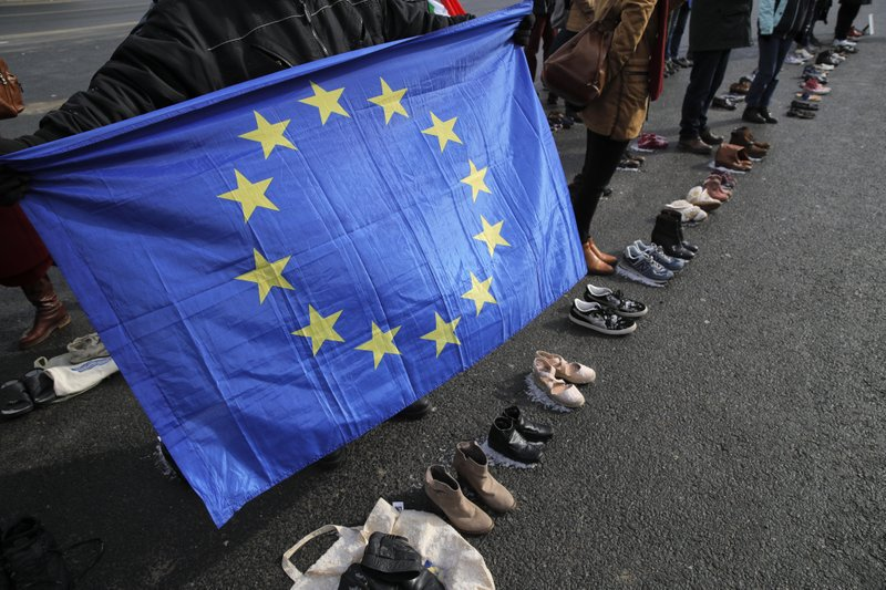 A man holds an European Union flag as people stand by shoes of Moldovan citizens working abroad are placed on the pavement in Chisinau, Moldova, Saturday, Feb. (AP Photo/Vadim Ghirda)