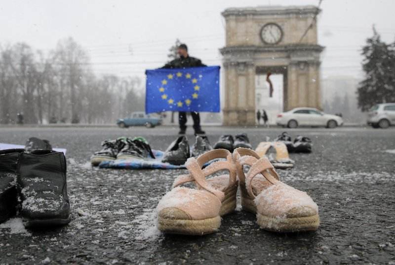 A man holds a European Union flag as people stand by shoes of Moldovan citizens working abroad are placed on the pavement in Chisinau, Moldova, Saturday, Feb. (AP Photo/Vadim Ghirda)