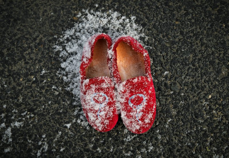 The slippers of 34 year-old Adela, a citizen of Moldova working in Sweden, are powdered with snow after her mother placed them on the pavement in Chisinau, Moldova, Saturday, Feb. (AP Photo/Vadim Ghirda)