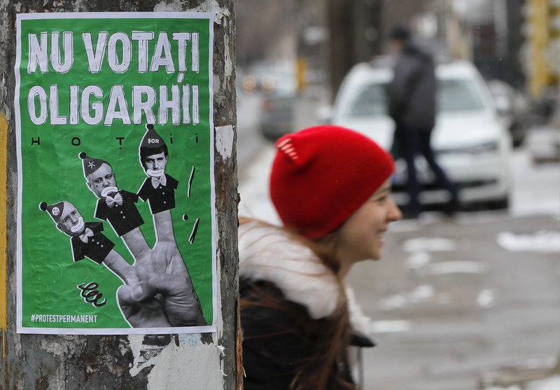 A child walks by a poster depicting, from left, Moldova's Prime Minister Pavel Filip, President Igor Dodon and Israeli born Modovan businessman and politician Ilan Shor, which reads