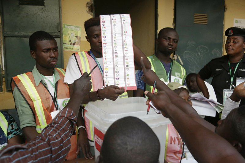 Party agents argue with electoral commission officials on a ballots the claim it was valid for the presidential race after the Gwadabawa polling station closed in Yola, Nigeria, Saturday Feb. (AP Photo/Sunday Alamba)