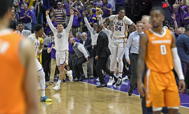 The LSU bench erupts as Tennessee player walk off the floor as time runs out in overtime of an NCAA college basketball game, Saturday, Feb. (AP Photo/Bill Feig)