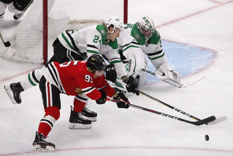 Chicago Blackhawks right wing Dylan Sikura (95) battles Dallas Stars left wing Roope Hintz (24) and goaltender Anton Khudobin (35) for the puck during the third period of an NHL hockey game Sunday, Feb. (AP Photo/Jeff Haynes)