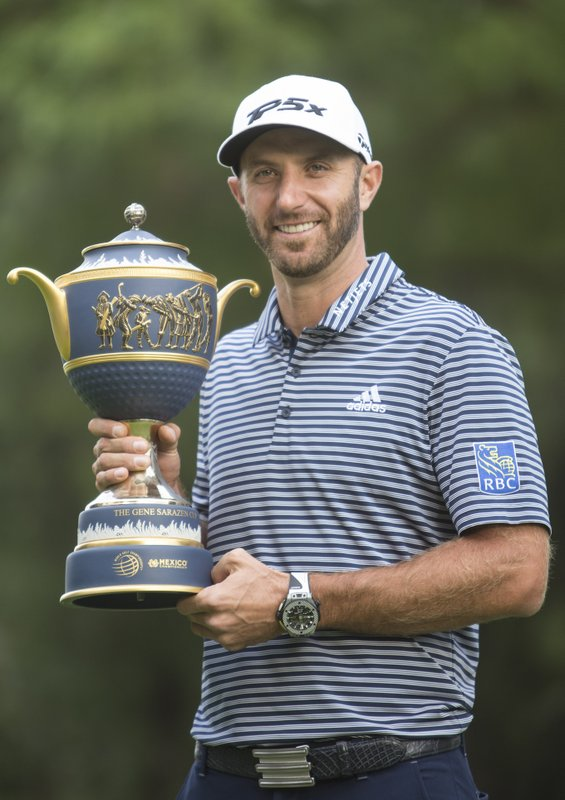 U.S. golfer Dustin Johnson poses with his Mexico Championship trophy at the Chapultepec Golf Club in Mexico City, Sunday, Feb. (AP Photo/Christian Palma)