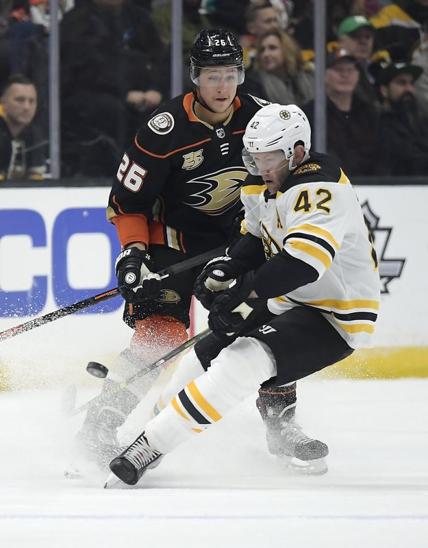 Boston Bruins right wing David Backes, right, takes the puck as Anaheim Ducks defenseman Brandon Montour puts pressure on him during the second period of an NHL hockey game Friday, Feb. (AP Photo/Mark J. Terrill)
