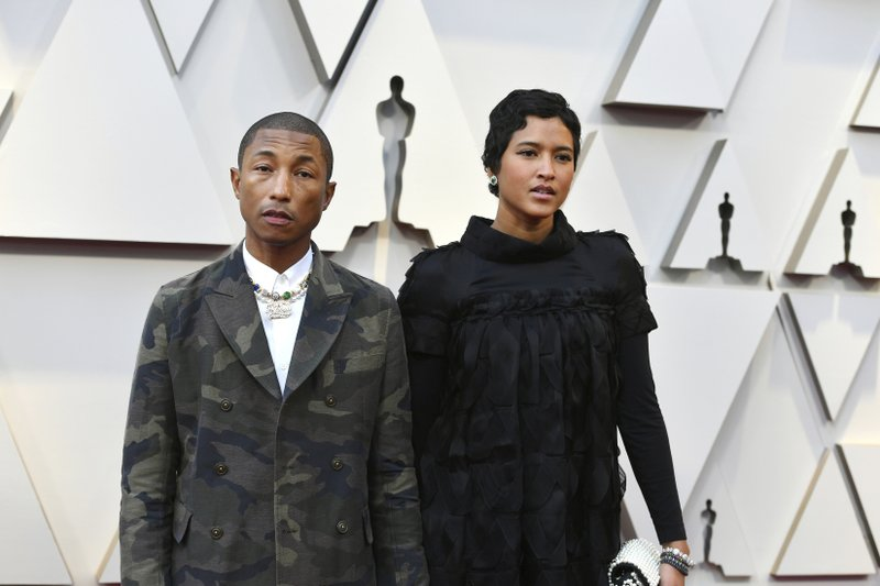 Pharrell Williams, left, and Helen Lasichanh arrive at the Oscars on Sunday, Feb. 24, 2019, at the Dolby Theatre in Los Angeles. (Photo by Jordan Strauss/Invision/AP)