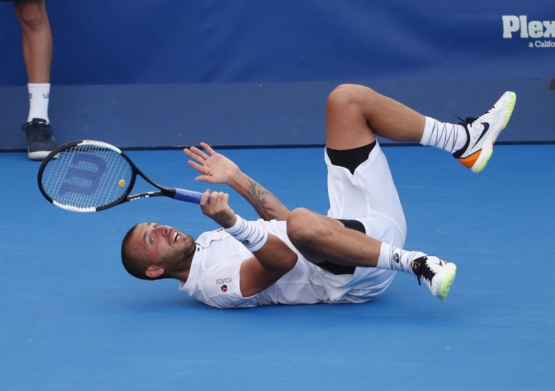 Daniel Evans, of Britain, tumbles after diving for a shot against Radu Albot, of Moldova, during the final tennis match at the Delray Beach Open, Sunday, Feb. (AP Photo/Wilfredo Lee)