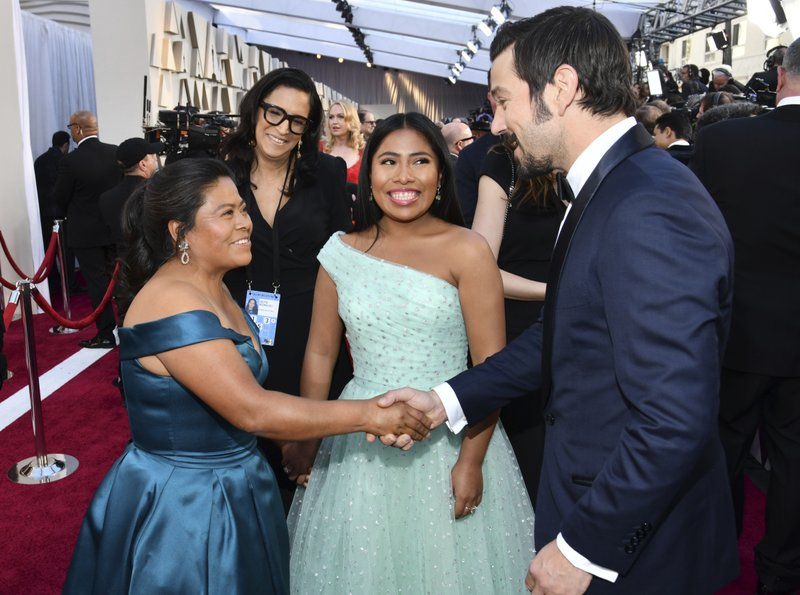 Margarita Martinez Merino, left, shakes hands with Diego Luna, right, as Yalitza Aparicio looks on during arrivals at the Oscars on Sunday, Feb. (Photo by Charles Sykes/Invision/AP)