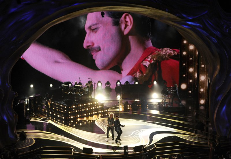 An image of Freddie Mercury appears on screen as Brian May, left, and Adam Lambert of Queen perform at the Oscars on Sunday, Feb. (Photo by Chris Pizzello/Invision/AP)