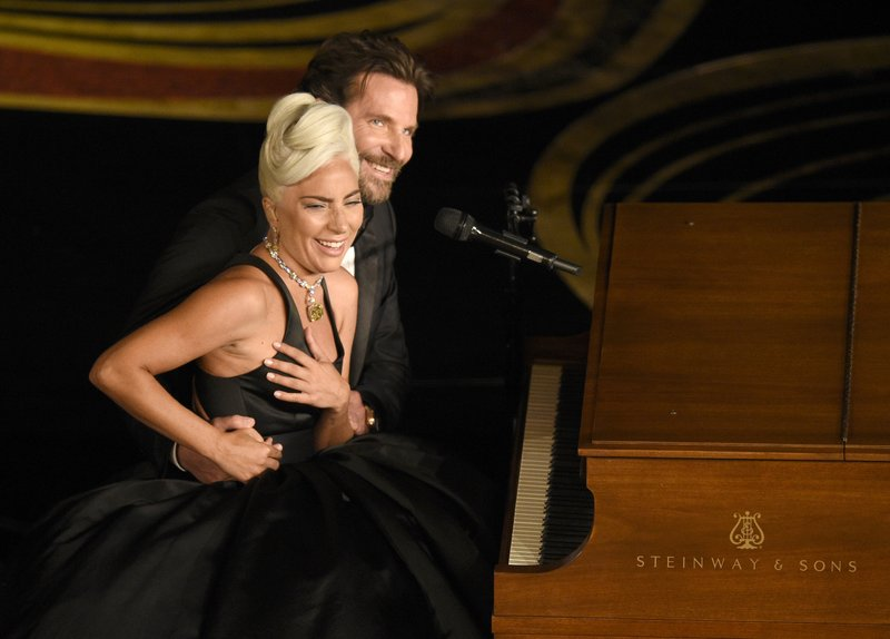Lady Gaga, left, and Bradley Cooper react to the audience after a performance of