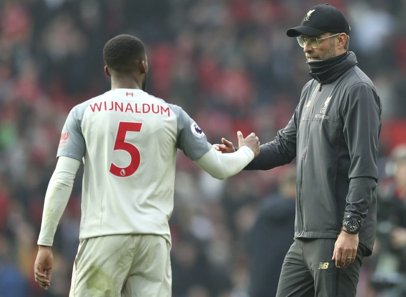 Liverpool manager Juergen Klopp, right, shakes hands with Liverpool's Georginio Wijnaldum at the end of the English Premier League soccer match between Manchester United and Liverpool at Old Trafford stadium in Manchester, England, Sunday, Feb. (AP Photo/Jon Super)