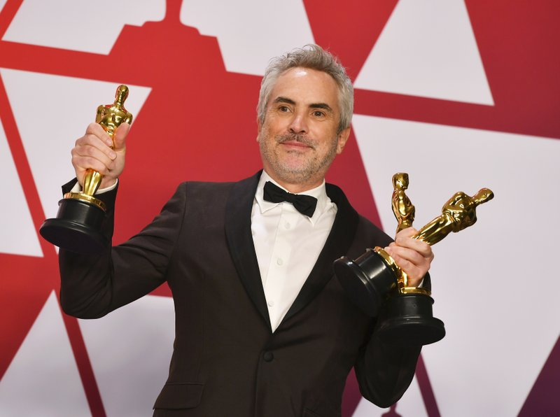 Alfonso Cuaron poses with the awards for best director for