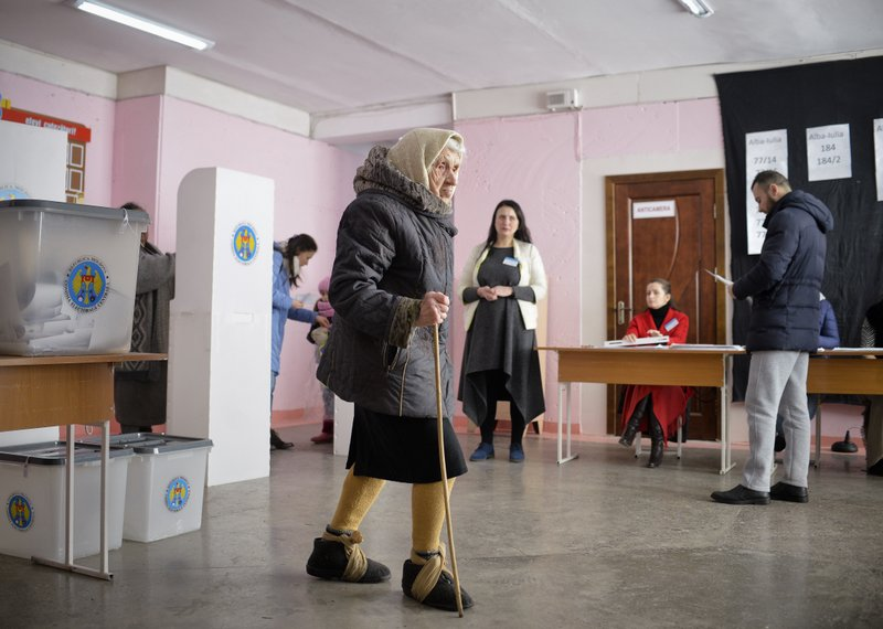 An elderly woman with cloth wrapped around her shoes to prevent her from slipping on ice walks after casting her vote in Chisinau, Moldova, Sunday, Feb. (AP Photo/Andreea Alexandru)