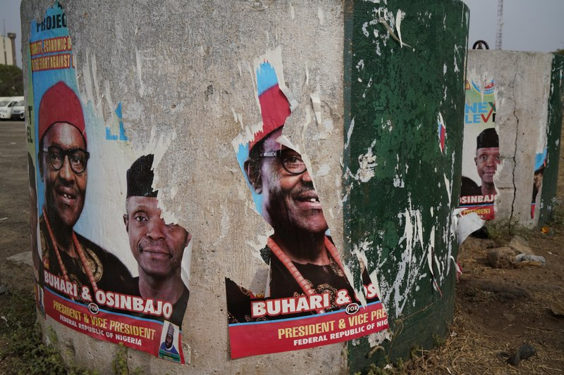 Torn posters of Nigerian Incumbent President Muhammadu Buhari are seen in Abuja Sunday Feb. 24, 2019. (AP Photo/Jerome Delay)
