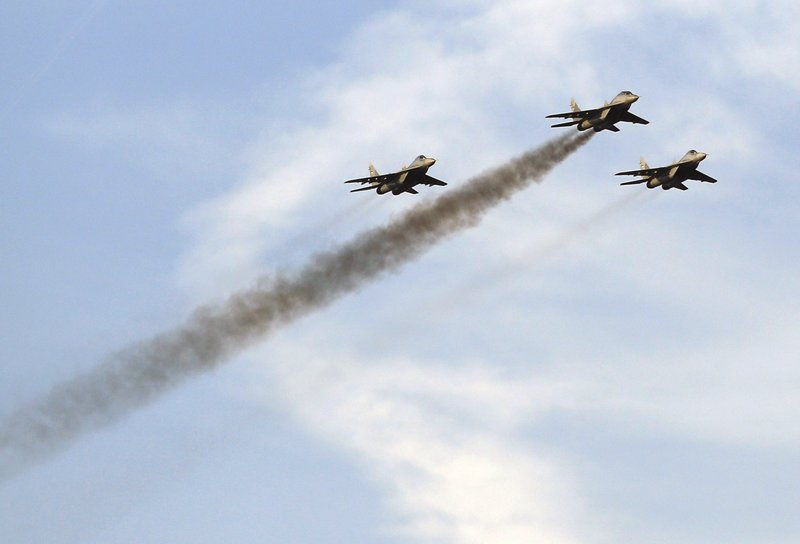 In this photo taken on Tuesday, Oct. 17, 2017, Serbian Army MiG-29 jet fighters perform over the military airport Batajnica, near Belgrade, Serbia. (AP Photo/Darko Vojinovic)
