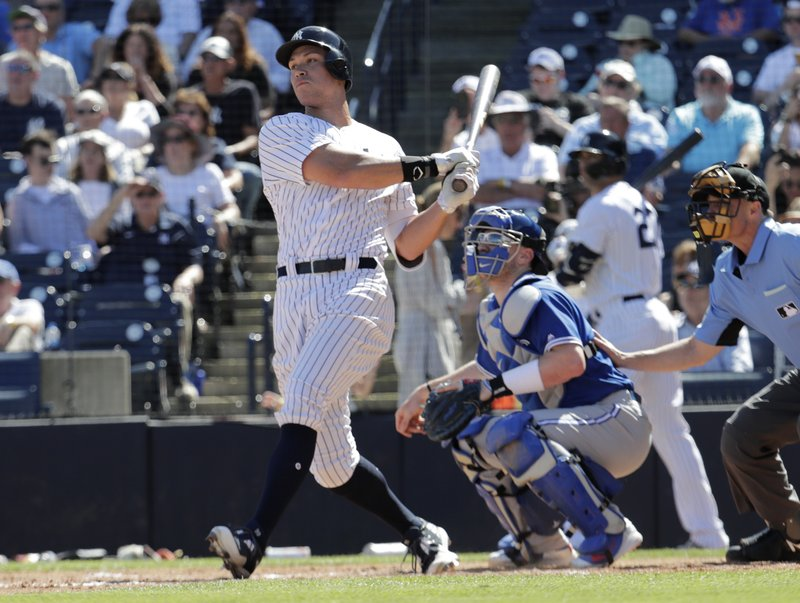 New York Yankees' Aaron Judge, left, follows through on a double in the third inning during a spring training baseball game against the Toronto Blue Jays, Monday, Feb. (AP Photo/Lynne Sladky)