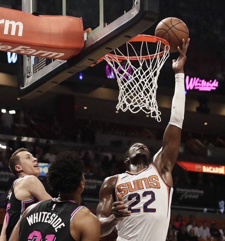 Phoenix Suns center Deandre Ayton (22) shoots and scores against Miami Heat forward Duncan Robinson (55) and Miami Heat center Hassan Whiteside (21) during the first half of an NBA basketball game Monday, Feb. (AP Photo/Brynn Anderson)