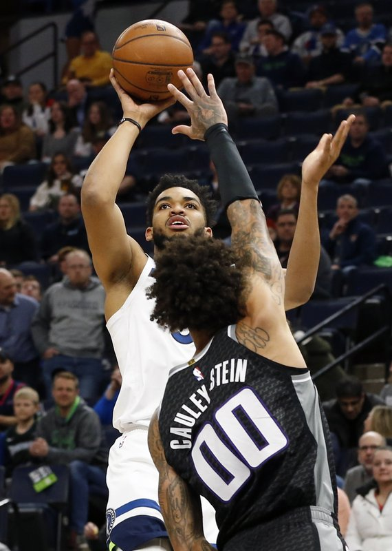 Minnesota Timberwolves' Karl-Anthony Towns, left, shoots over Sacramento Kings' Willie Cauley-Stein in the first half of an NBA basketball game Monday, Feb. (AP Photo/Jim Mone)
