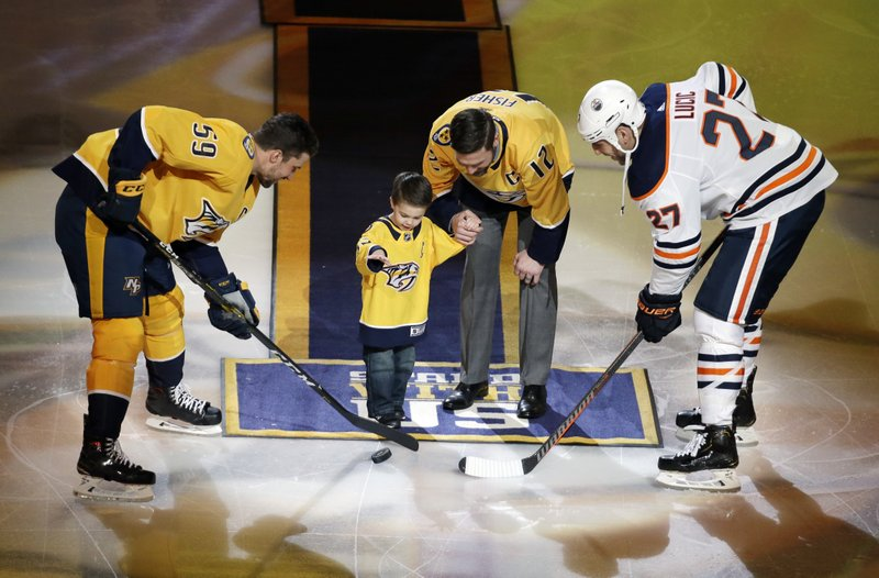 Former Nashville Predators center and captain Mike Fisher watches as his son, Isaiah, drops a ceremonial puck for Predators defenseman Roman Josi (59), of Switzerland, and Edmonton Oilers left wing Milan Lucic (27) as Mike Fisher is honored before an NHL hockey game Monday, Feb. (AP Photo/Mark Humphrey)