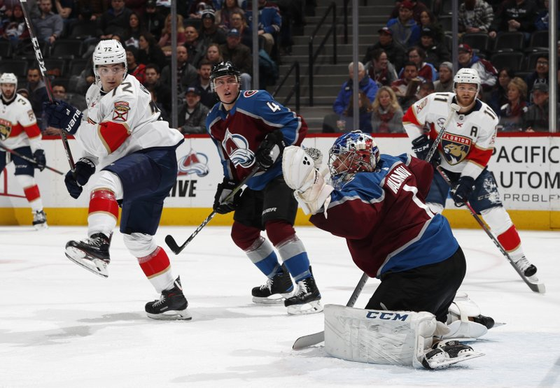 Florida Panthers center Frank Vatrano, left, looks on with Colorado Avalanche defenseman Tyson Barrie as goalie Semyon Varlaov makes a glove-save of a shot in the second period of an NHL hockey game Monday, Feb. (AP Photo/David Zalubowski)